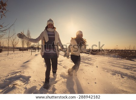 Two girlfriends have fun and enjoy fresh snow at beautiful winter day - stock photo