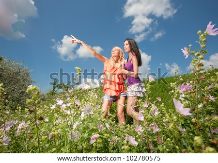 two girlfriends having fun in field
