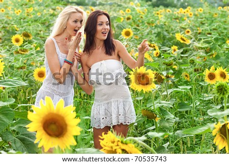two girlfriends having fun in field sunflowers - stock photo