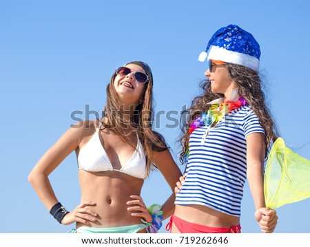 Two girlfriends in a Santa hat and in the image of a pirate during a beach holiday. Christmas, holidays and people concept - friendship and fun
