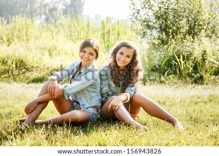 two girlfriends in jeans wear sitting on grass smiling looking at camera