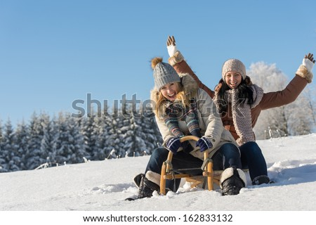 Two girlfriends sledge downhill in sunny wintertime snow wooden sledge - stock photo