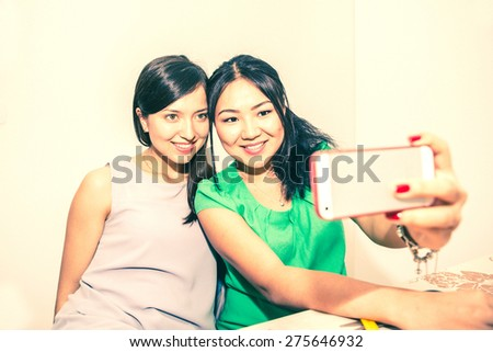 Two girlfriends taking a selfie with smart phone - Happy women having fun at party - Young multiracial couple of girls sending their photo to friends with wireless internet - stock photo