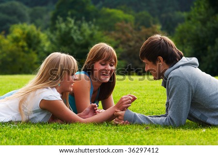 Two girls and one guy flirting in a meadow - stock photo