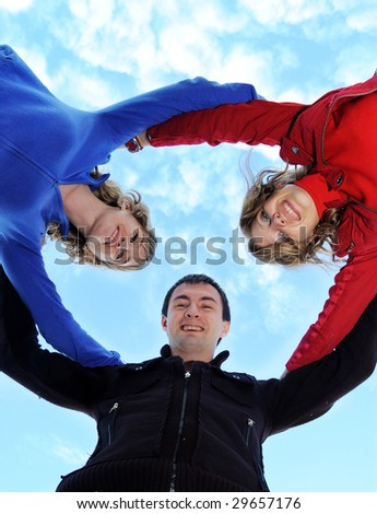 Two girls and the guy stand together and look at cam - stock photo