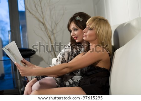 Two girls are discussing an article in a magazine while sitting on a white couch