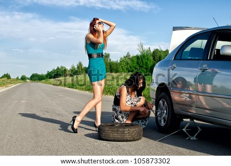Two girls are fixing a changing a tire. - stock photo