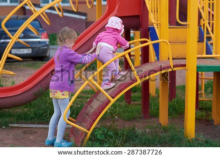 Two girls are playing on the playground in the spring - stock photo