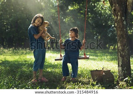 Two girls are playing with a puppy under the tree. - stock photo
