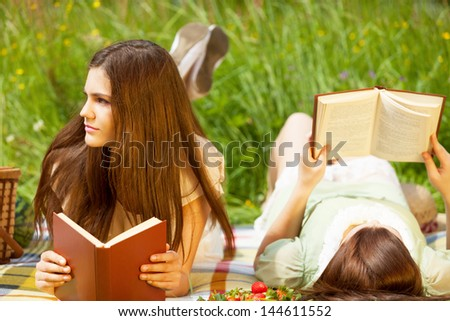 Two girls are resting in park with books - stock photo