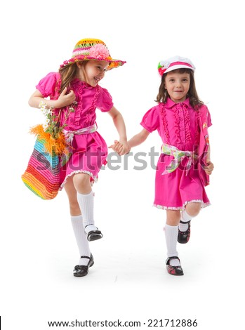 Two girls are walking on a white background. They are laughing and talking with each other. They have beach bags. They are dressed for summer.