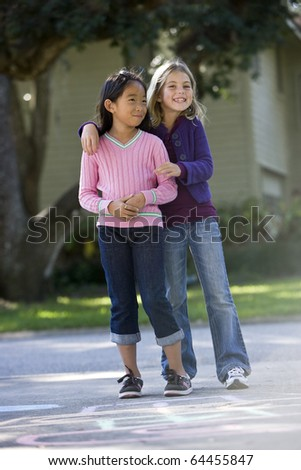 Two girls at home on driveway standing in front of hopscotch board (7 years) - stock photo