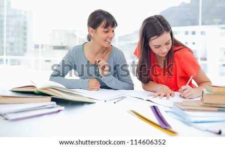 Two girls at the table studying together as they finish their homework - stock photo