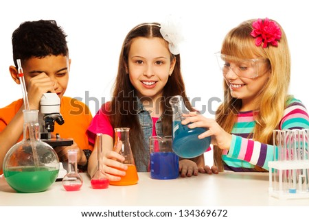 Two girls blond and brunet and black boy, with microscope, test tubes and flasks conducting experiments, isolated on white - stock photo