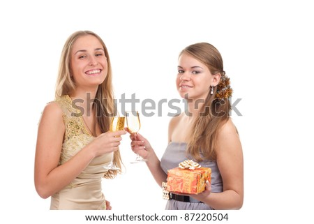 Two girls celebrate Christmas with gifts and glasses in their hands studio shooting