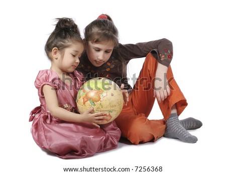 Two girls consider globe on white background - stock photo