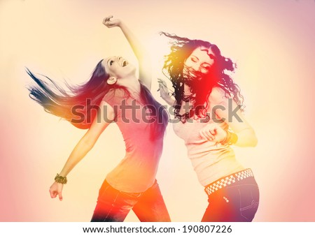 two girls dancing, retro light leak design - stock photo