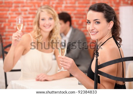two girls dressed in robes toasting in a restaurant - stock photo