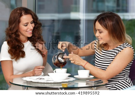Two girls drink tea in cafe and talking