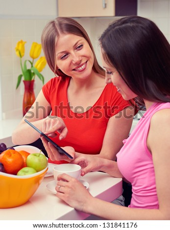two girls drinking coffee and using tablet pc - stock photo