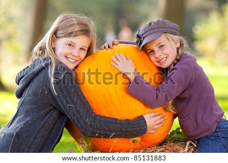 two girls embrace their big pumpkin - stock photo
