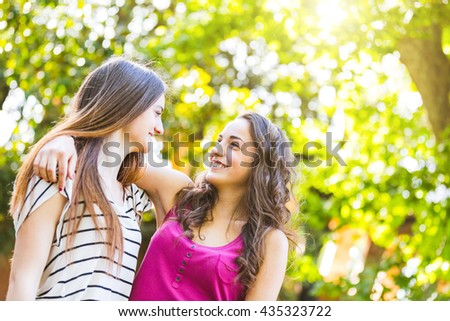 Two girls embraced together at park. They are happy and smiling while looking each other. Best friends embracing with trees on background. Lifestyle and friendship concepts. - stock photo