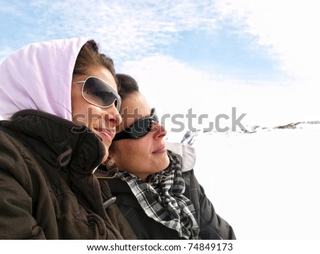 Two girls enjoying in the snow - stock photo