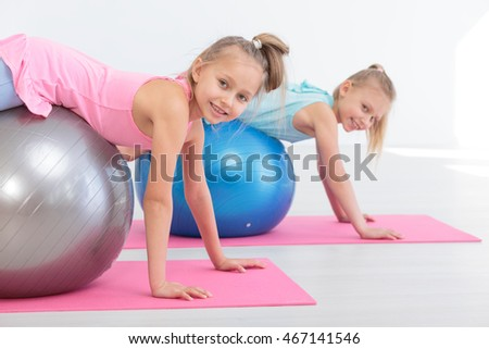 Two girls exercising with exercise ball on mat