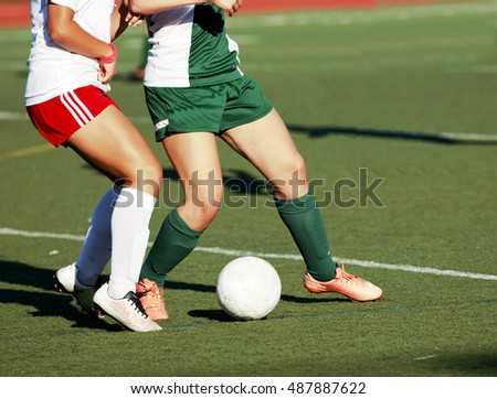 two girls fight for posession of the soccer ball during a game
