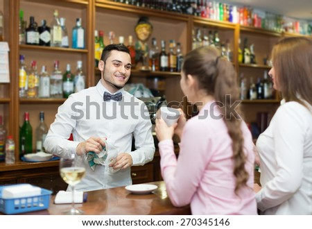 Two girls flirting with handsome barman