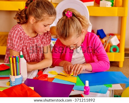 Two girls friend  kids gossip and craft colored paper on table in kindergarten . - stock photo