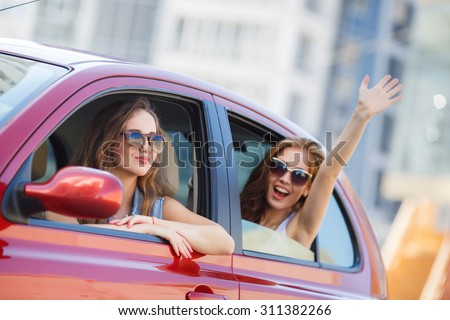 two girls friends in car. summer vacation. Friends going on road trip travel on summer day. freedom. cheering joyful with arms raised - stock photo