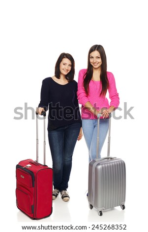 Two girls friends standing in full length with travel suitcases smiling happy, isolated on white background. - stock photo