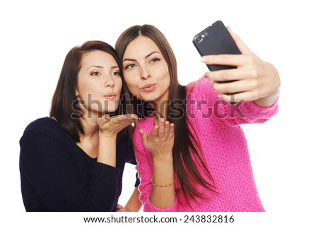 Two girls friends taking selfie with smartphone, blowing a kiss in the camera, isolated on white background - stock photo