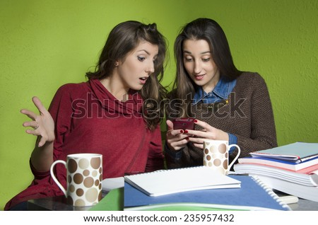Two girls gossiping while, they are on a break from studying. Looking at smart phone stunned, social networking. Selective focus on first girl - stock photo