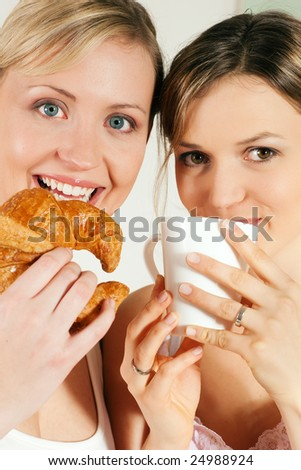 Two girls having coffee and croissants for breakfast - stock photo