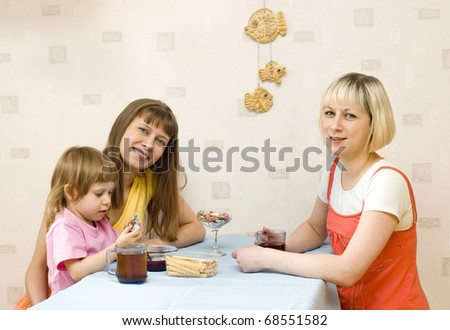 Two girls having tea at the table - stock photo