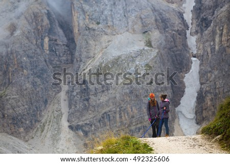 two girls hiker with a backpack standing at the mountains Dolomites, Italy