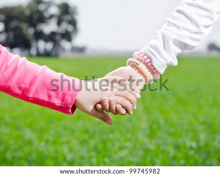 two girls holding hands on a green background of nature