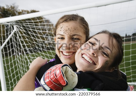 Two girls hugging in front of soccer net - stock photo