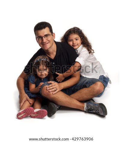 Two girls hugging their father - stock photo