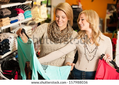 Two girls in a clothes shop - women in shopping - stock photo