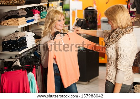 Two girls in a clothes shop- women shopping - stock photo