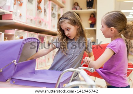 Two girls in a toy store with dolls look into the buggy, focus on left girl - stock photo