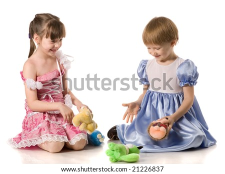 Two girls in beautiful dresses playing with toys on the floor, isolated on white
