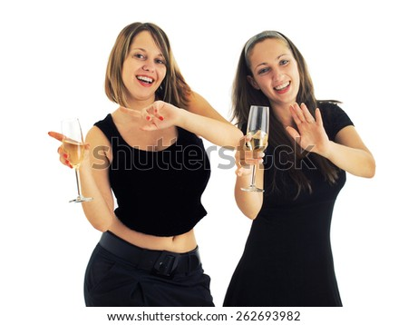 Two girls in black formal wear dancing with champagne glasses (could be an office party) - stock photo