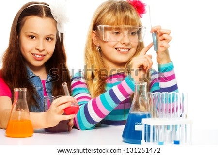 Two girls in chemistry lab class with test tubes and flasks conducting experiments, isolated on white - stock photo