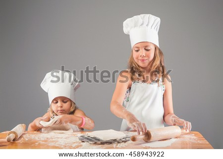 Two girls in clothes cooks on a wooden table with a rolling pin knead the dough from flour