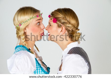 Two girls in dirndls have a argument - stock photo