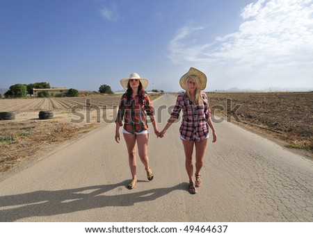 Two girls in late teens walking down a country road holding hands.